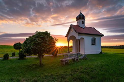 Sonnenuntergang an einer Kapelle in Bayern