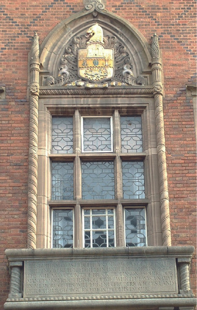 The central window has a projecting stone balcony incorporating a memorial tablet
