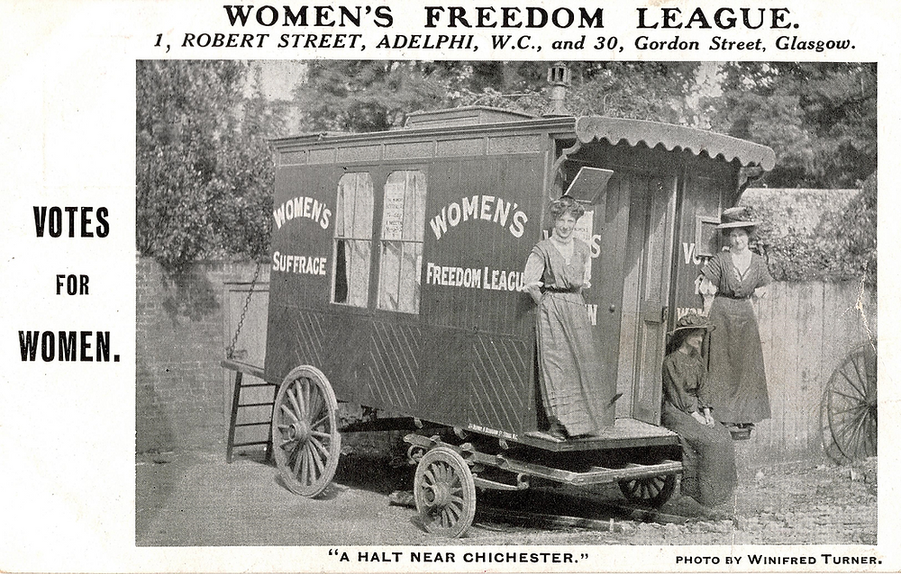 Promotional postcard featuring the WFL's suffrage caravan, probably in a yard in St Pancras, Chichester, with Muriel Matters on the left and possibly Madge Turner on the right (London School of Economics, TWL.2002.327)