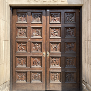 Large oak doors are carved with 20 scenes representing police activities