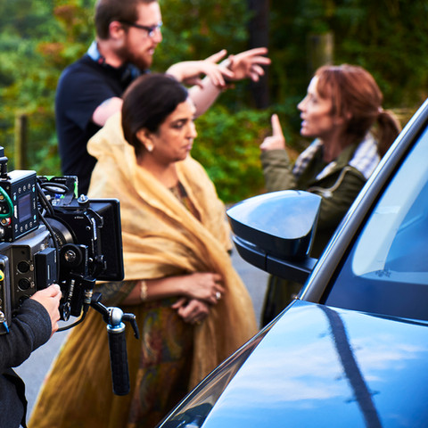 Jenni Suitiala frames the shot whilst the cast and director rehearse.