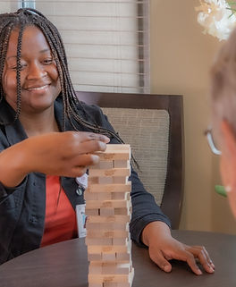 Staff member playing Jenga with resident