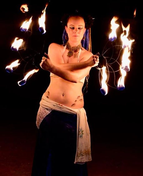 Noora Amar holding a pair of fire fans crossed in front of her