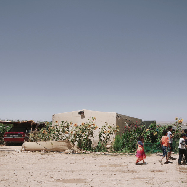 Syrian children walking past a neighbor's house in an informal refugee camp