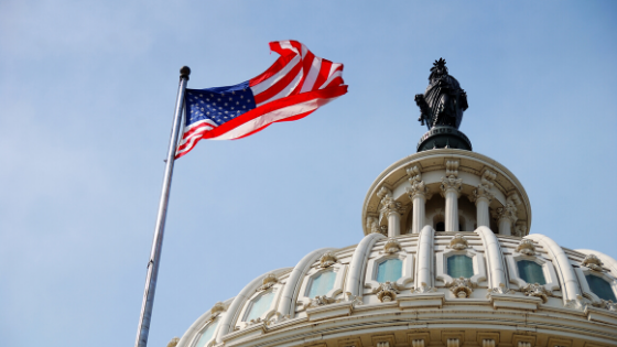 American flag flying over Capitol building in DC.