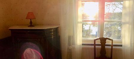 Auringonlasku näkyy huoneen ikkunasta
