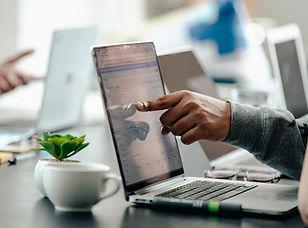 man-pointing-at-laptop-screen-analytics.