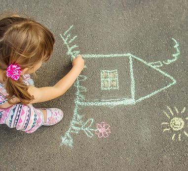 child-draws-house-with-chalk-asphalt-sel