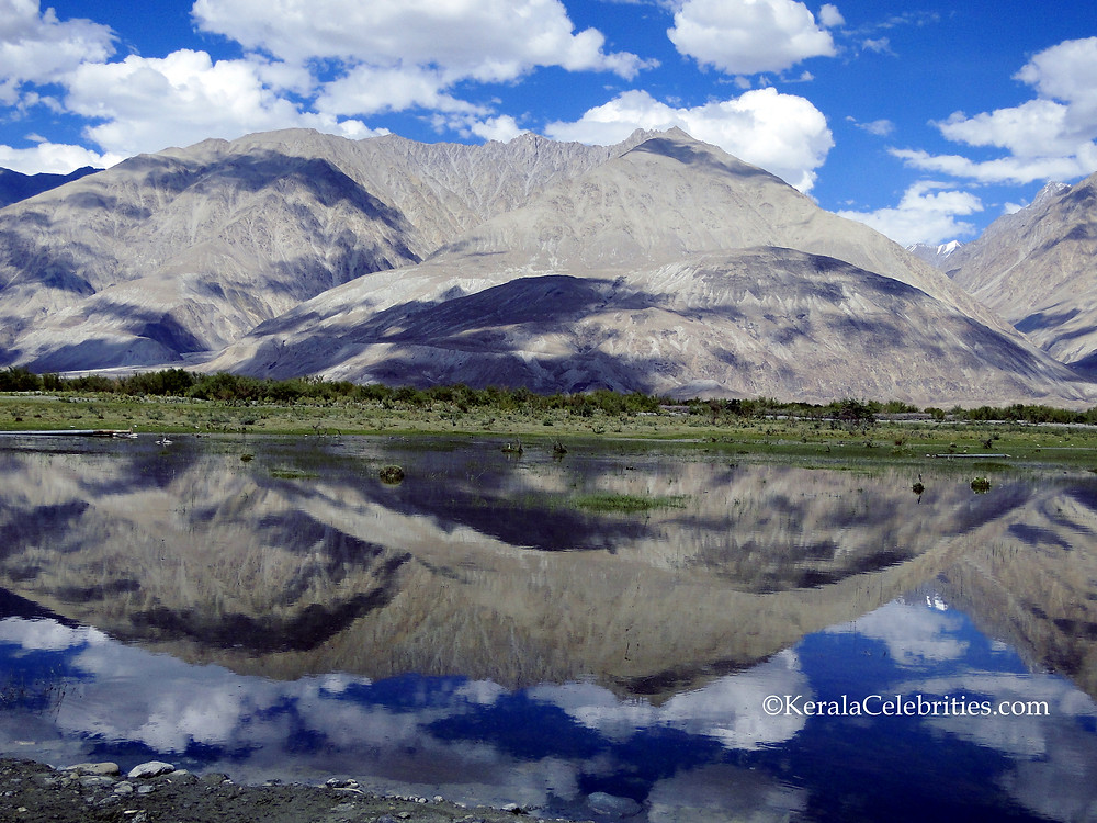 Mirror-view of a mountain over crystal clear water on the way