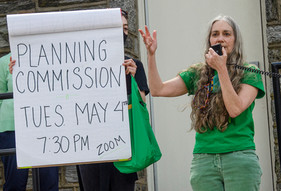 """Woman speaking into microphone next to sign: """"Planning Commission Tues May 4, 7:30 Zoom"""""""