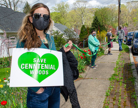 """Woman holding sign """"Save Centennial Woods"""" and ribbon connecting to a chain of people"""