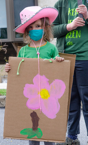 Young girl with pink cowboy hat, green shirt, and painted sign with a flower