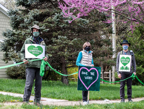 Tree people holding signs and a green ribbon connecting them