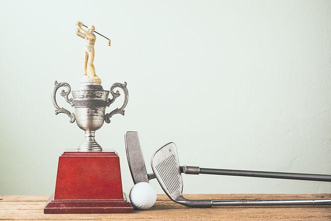 Palos de golf, bolas y trofeo