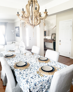 White dining room with light gray walls and neutral colors. Blue pattern tablecloth and skirted diningroom chairs. woven straw placemats, dark blue plates and glass apothecary jar decor