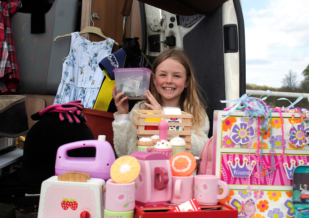 Girl grinning, holding up her takings from her car boot stall