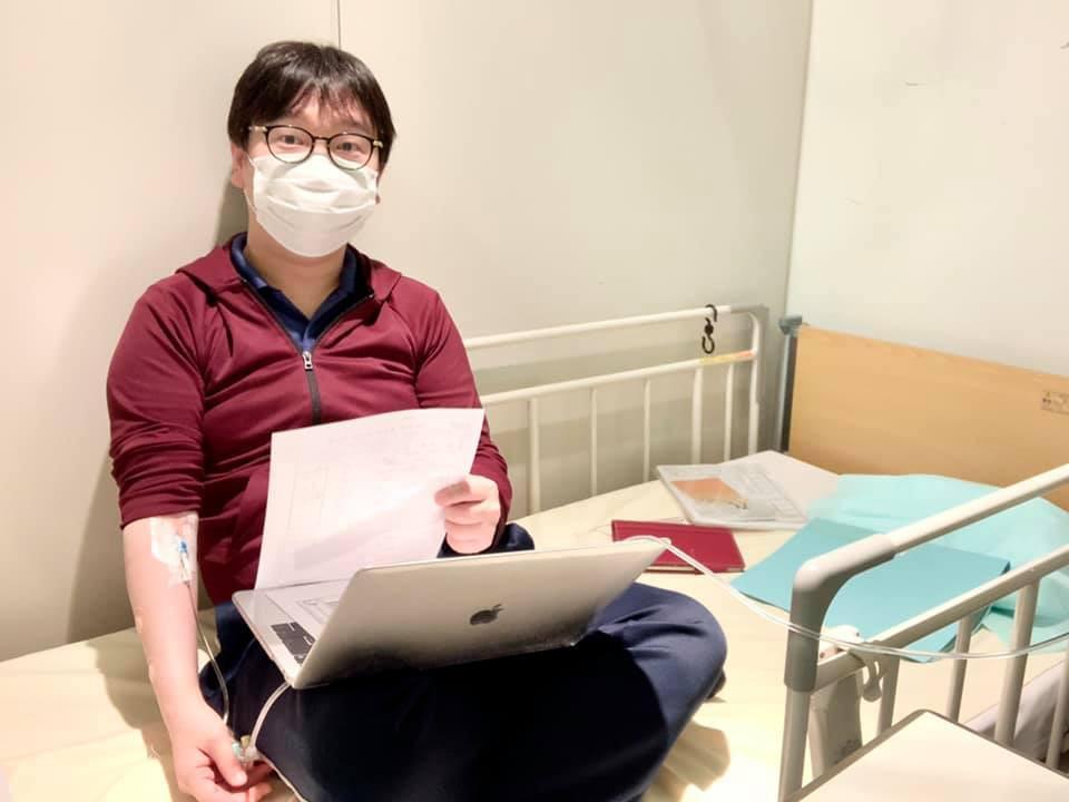 病室で治療を受けながら仕事をする様子