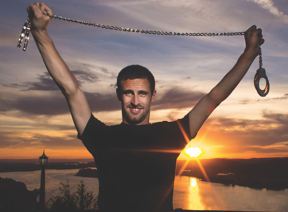 photo of Blake Shelley holding a chain with both hands up in the air with sunset behind him