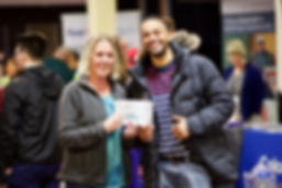A man and woman holding a silver ticket