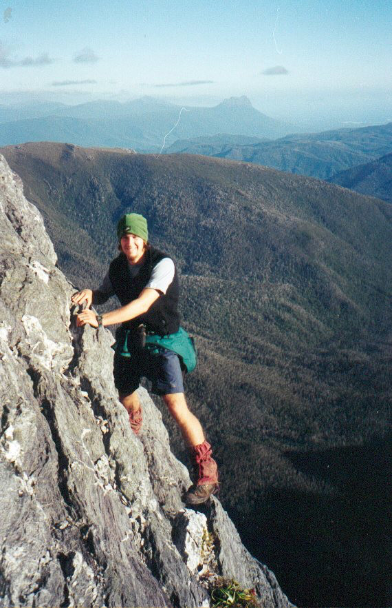 Patrice scaling Federation Peak with Precipitous Bluff behind.