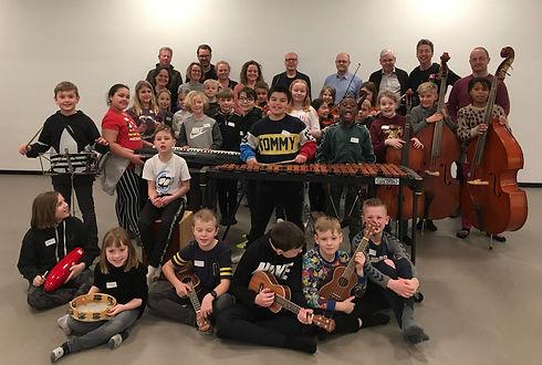 Orkester mester elever med lærer i baggrunden