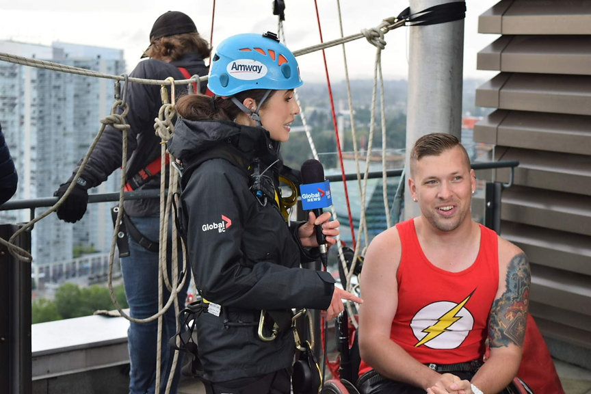 Marco being interviewed on Global BC News before rappelling off of a 20-storey building in his chair