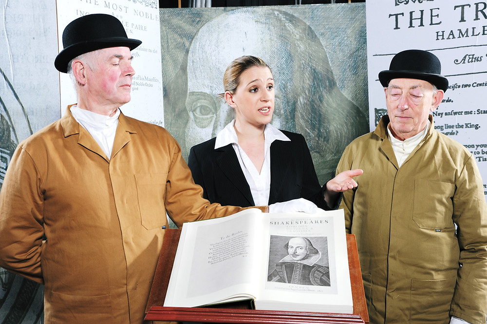 Still from the 2010 Malvern Theatre Players production of Nay, Remember Me! by Amelia Marriette. A Comedy Drama about the printing of the First Folio of 1623.  Mike Fray, Porter, Lucy Fothergill, Auctioneer and Chris Green, Porter. Photograph courtesy of Malvern Theatre Players.