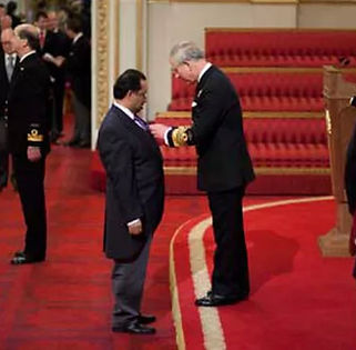 Bajloor Rashid receiving MBE from Prince