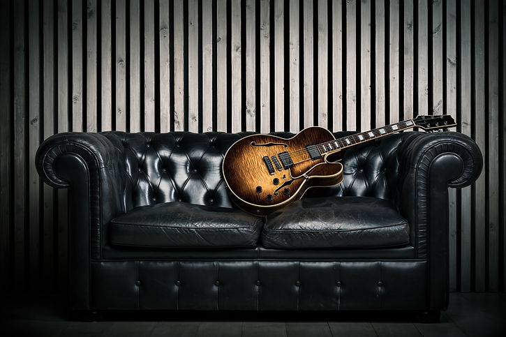 empty vintage sofa and electric guitar w