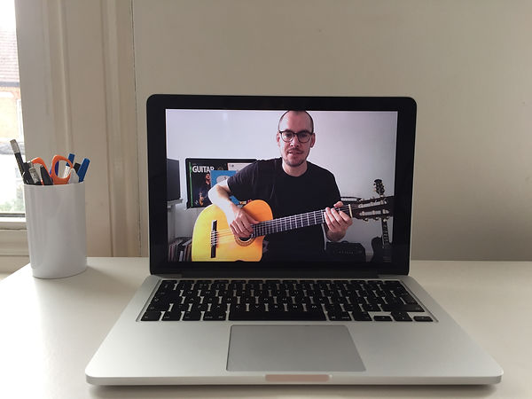 Online guitar teacher appears on laptop