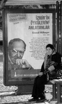 """İzmir Büyükşehir Belediyesi """"Dünya Öykü Günü"""" etkinlikleri kapsamında otobüs duraklarındaki reklam panolarında Kemal Bilbaşar da dahil olmak üzere, """"İzmir'in Öykulerini Anlatan"""" önde gelen yazarları sergiledi (Şubat 2019)"""