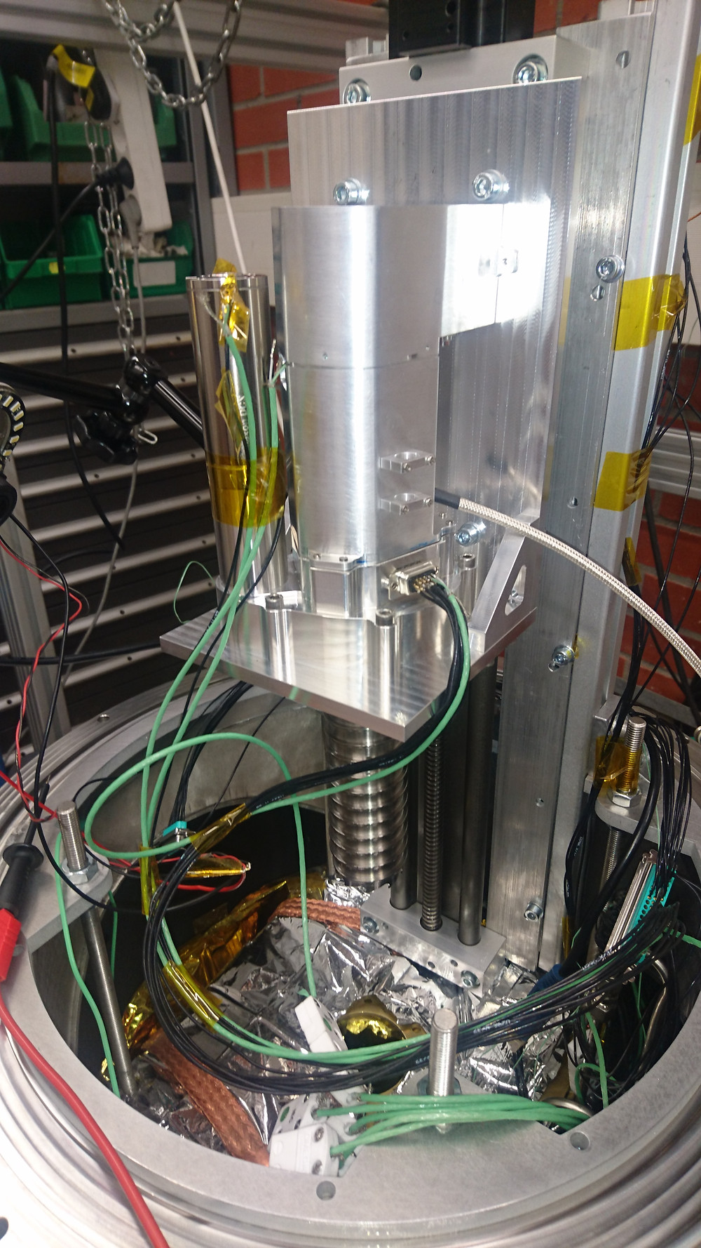 The integrated instrument in the thermal vacuum chamber. The drill is mounted on a linear guide to allow the drilling, heating and gas extraction in simulated lunar conditions.
