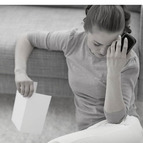 Woman suffering from anxiety, women with stress, woman with anxiety, women sitting on floor, hand on forehead, phone in hand, women sitting next to coach, room, anxious, worried, depressed, woman, jersey, greyscal, beautiful woman, alone, floor, tired, upset, anxiety and worry. Selling gift boxes, wellbeing gift boxes, self-care gift boxes, anxiety relief in a box
