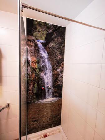 Duschrückwand mit Wunschmotiv und Nur-Glas-Dusche mit Drehtür