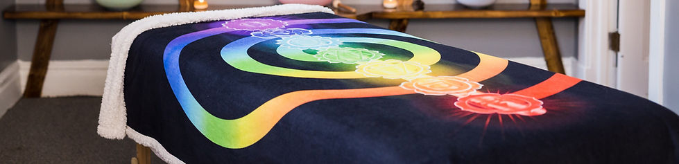 Massage bed with circular chakra colored blanket lit with light