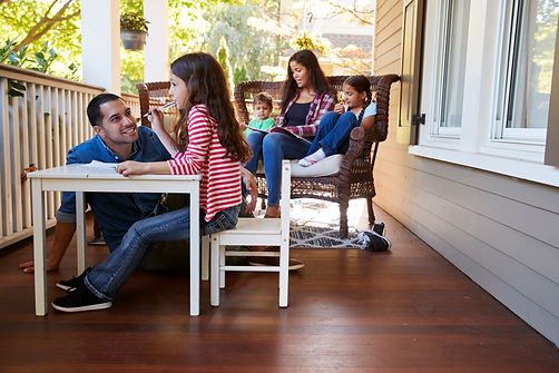 family-sit-on-porch-of-house-reading-books-and-pla-PHLNWKS.jpg