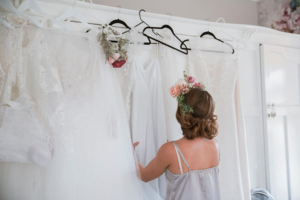Bride looking at wedding gown option in a fitting
