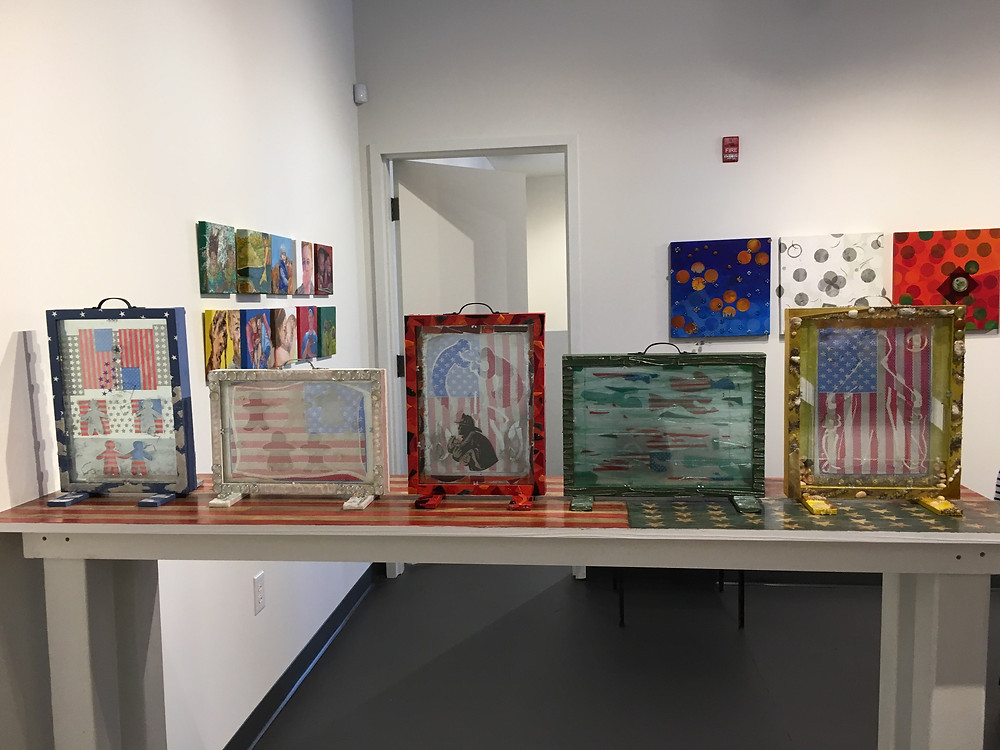 """Carol Taylor-Kearney.  """"American Prayer Flags:  Boxes-- Blue, White, Red, Green, Yellow"""" on """"American Flag"""", folk -art table.  Pictured on the left, """"American Prayer Flags:  Portraits""""; pictured on right, """"American Prayer Flags:  Construction"""" series."""