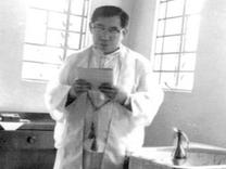 Fr. Carlo Ly the Parish Priest at the Baptismal Font at the back of the Church in the early 70s