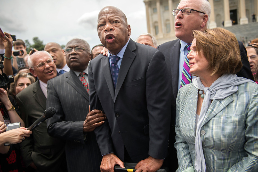 """UNITED STATES - JUNE 23: From left, Reps. Paul Tonko, D-N.Y., James Clyburn, D-S.C., John Lewis, D-Ga., Joe Crowley, D-N.Y., House Minority Leader Nancy Pelosi, D-Calif., Terri Sewell, D-Ala., and Charlie Rangel, D-N.Y., sing """"We Shall Overcome"""" with demonstrators on the East Front of the Capitol after the House Democrats' sit-in ended on the floor, June 23, 2016. The Democrats are calling on Republicans to allow a vote on gun violence measures. (Photo By Tom Williams/CQ Roll Call)"""