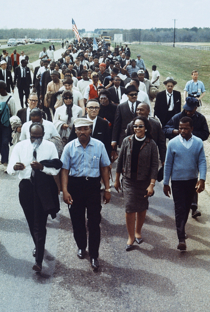 Martin Luther King Jr., (with hat) flanked by his wife Coretta (right) and John Lewis (far right), leads a march from Selma to Montgomery, Alabama, March 1965. (AP Photo)