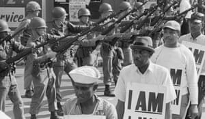 """National Guard troops stand with bayonets fixed as African-American sanitation workers march wearing placards reading """"I AM A MAN."""""""