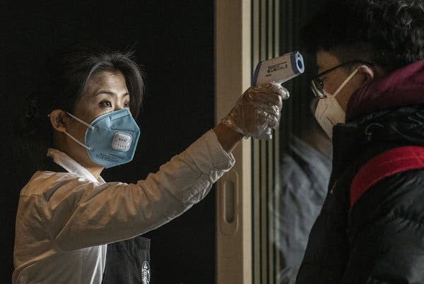 A worker at a Starbucks at an airport in Beijing in January checks a customer's temperature.