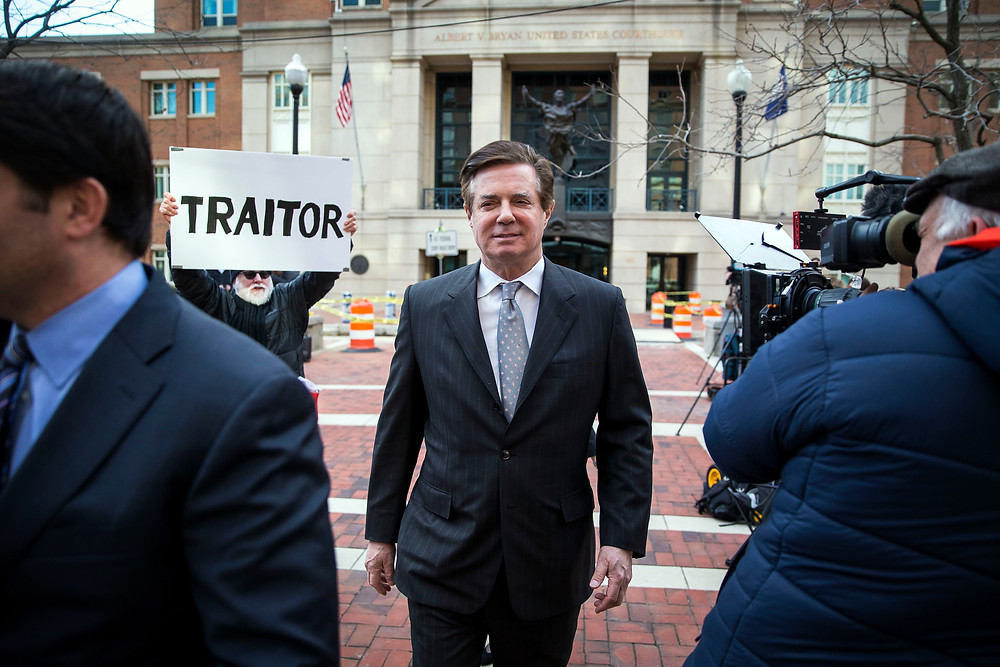 FILE -- Paul Manafort, President Donald Trump's former campaign chairman, departs with his spokesman, Jason Maloni, left, after his arraignment hearing, at the federal courthouse in Alexandria, Va., March 8, 2018. As Manafort's trial continues, questions about Russian involvement in Trump's 2016 campaign are not on the docket, but hang heavily over the proceedings. (Al Drago/The New York Times)