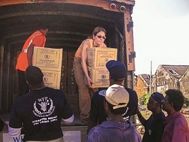 Leslie Boghosian Murphy handing two boxes of supplies to Sri Lankan citizens