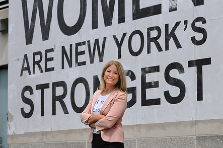 "Leslie Boghosian Murphy wearing a light pink blazer and crossing her arms in front of a billboard which reads ""Women are New York's Strongest"""