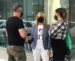 Leslie Boghosian Murphy wearing a mask and speaking with two residents at a community meeting.
