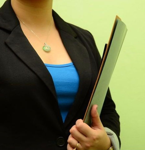 Person holding a clipboard and folder