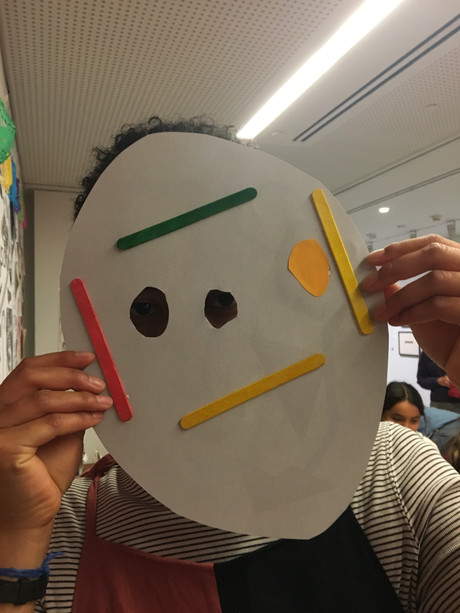 A participant displays their mask