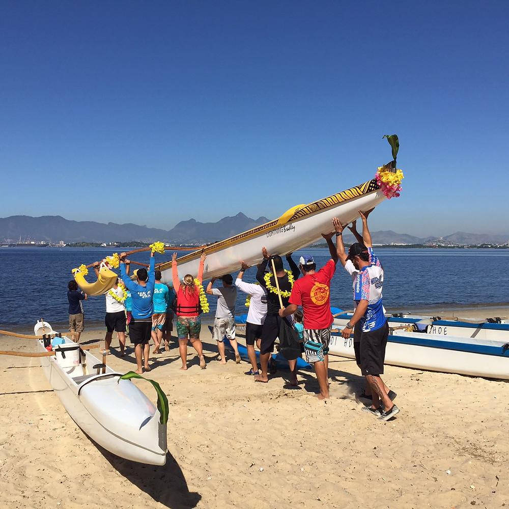canoa sendo levada à água do mar pela primeira vez
